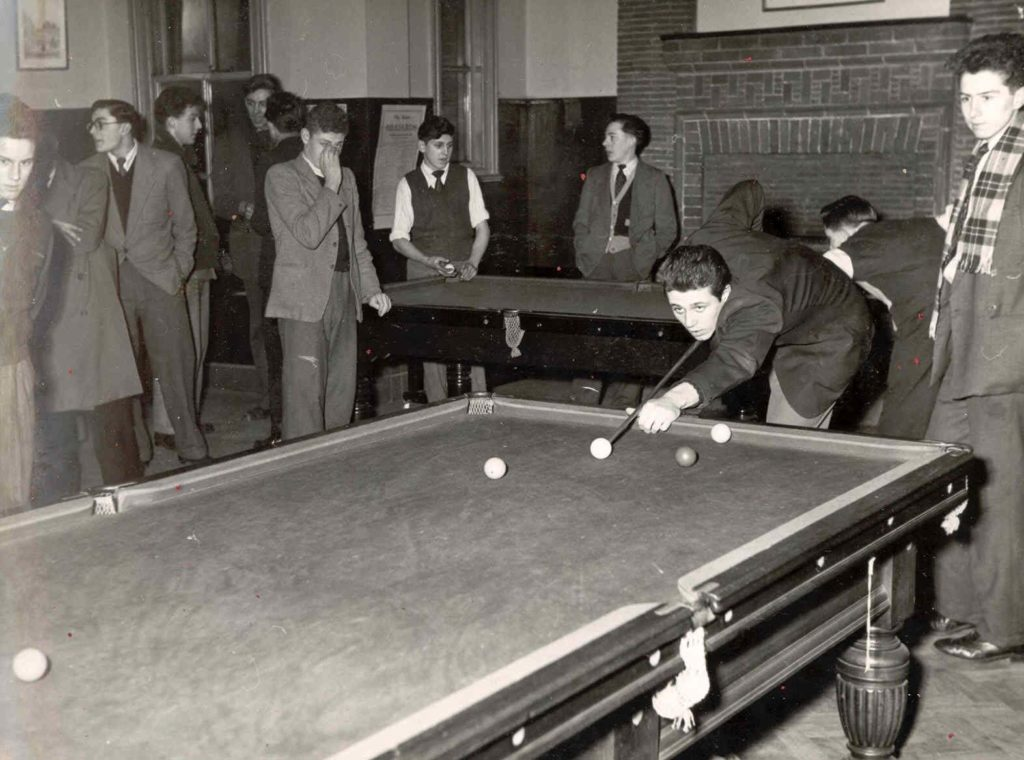 a black and white photograph of teenahe boys in suits and jackets playing pool