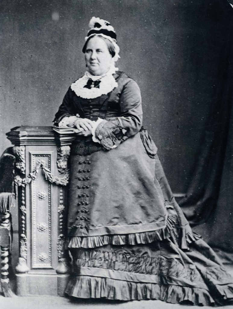 a black and white photo of a woman in Victorian dress