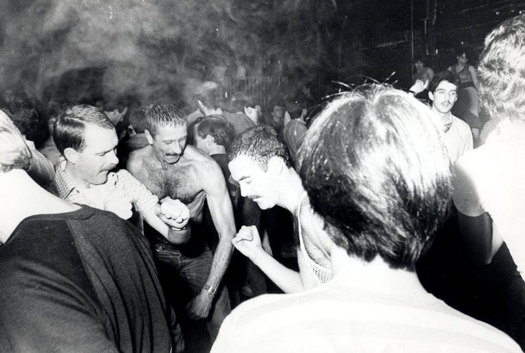 a black and white photo of sweaty men with moustaches dancing together
