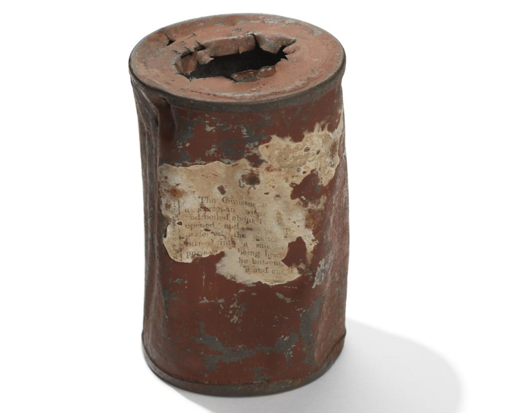 a photo of an old tin can with the remains of a label on its side