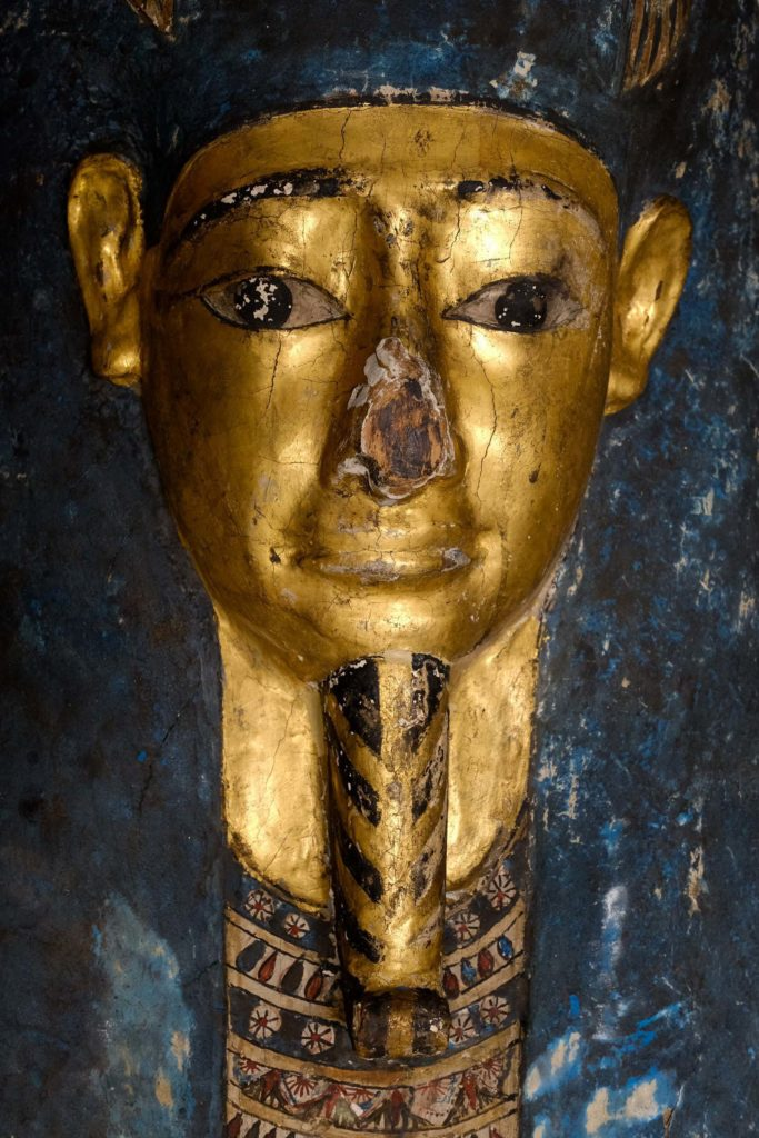 a close up of a golden mummy mask wit damaged nose