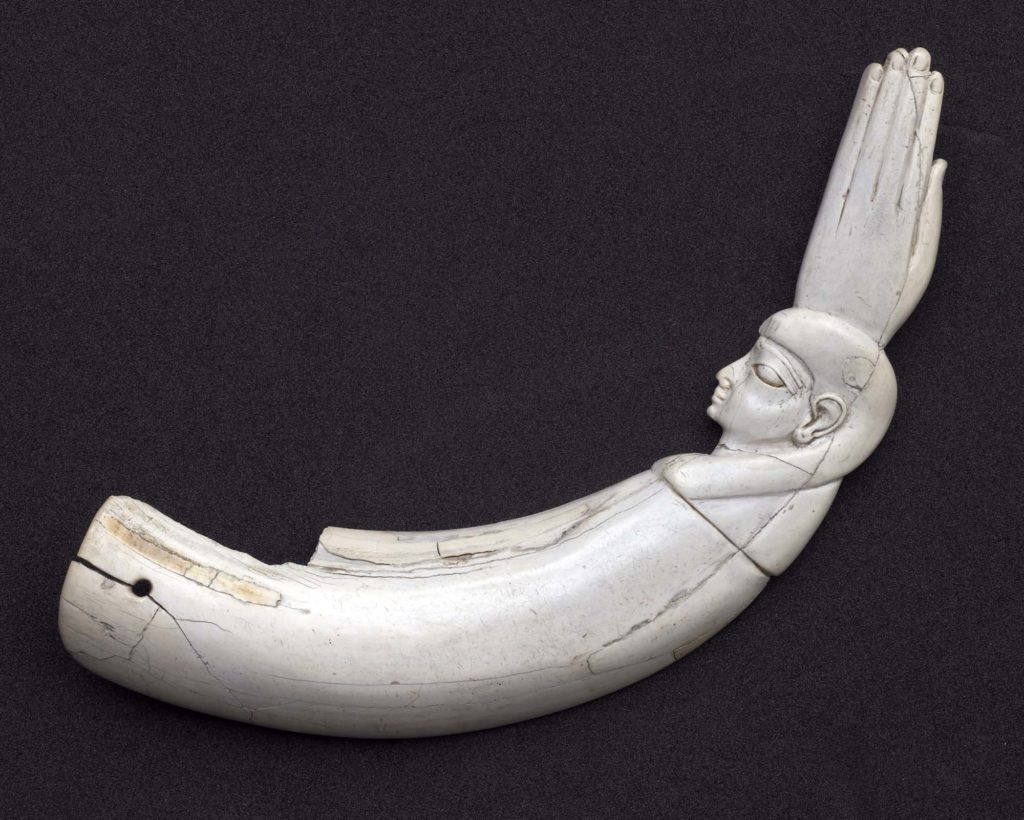 a photo of a shaped bone carving with a hand and face on one end