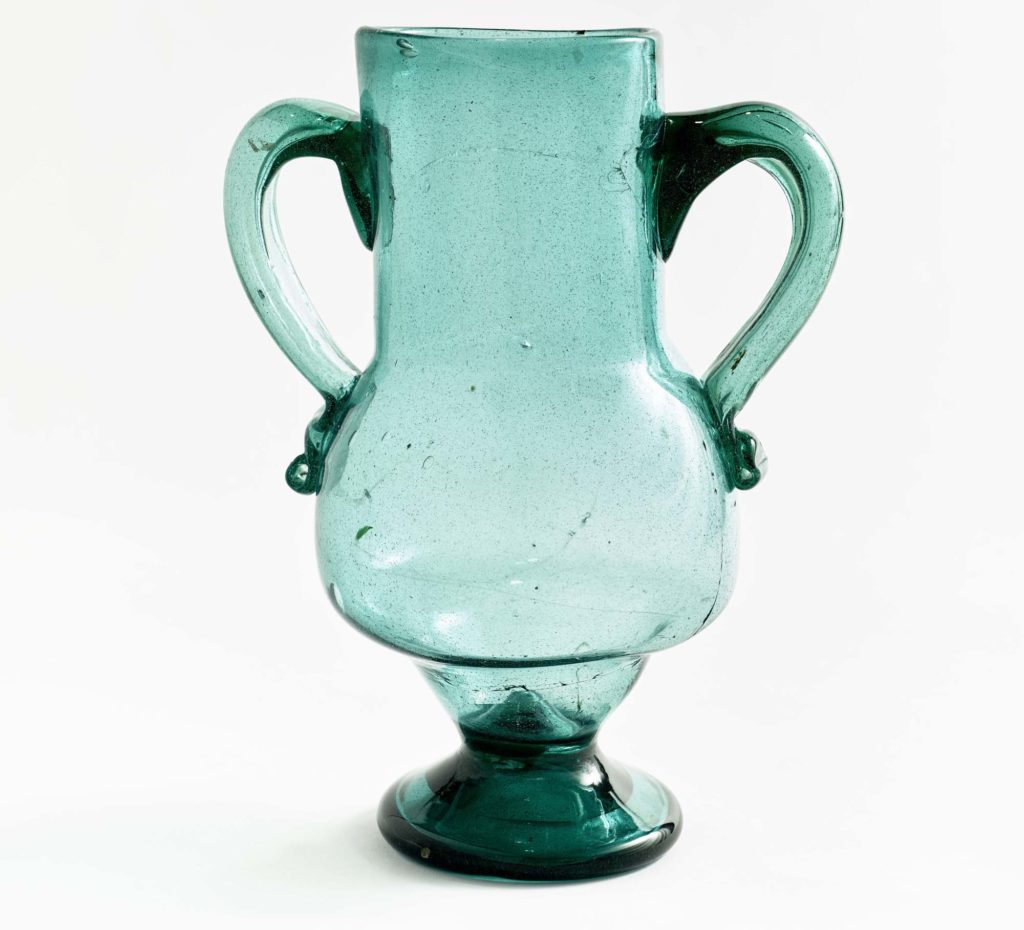 a photo of a blue glass vase with two handles