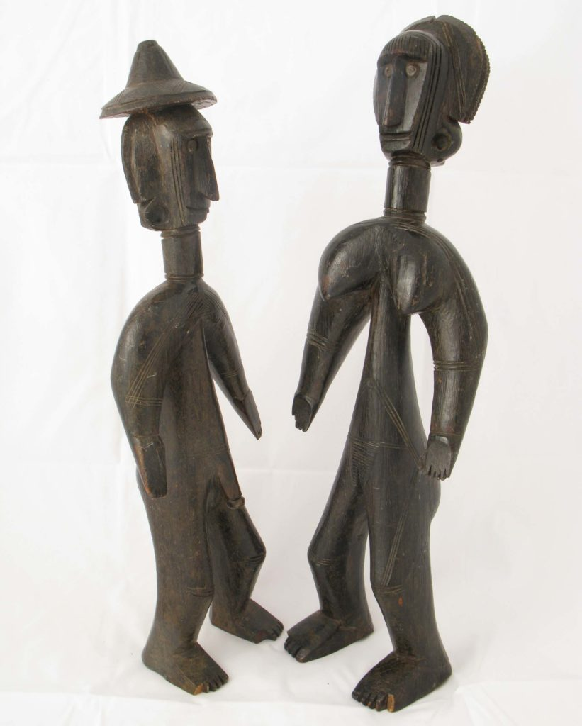 a photo of two figures carved in wood