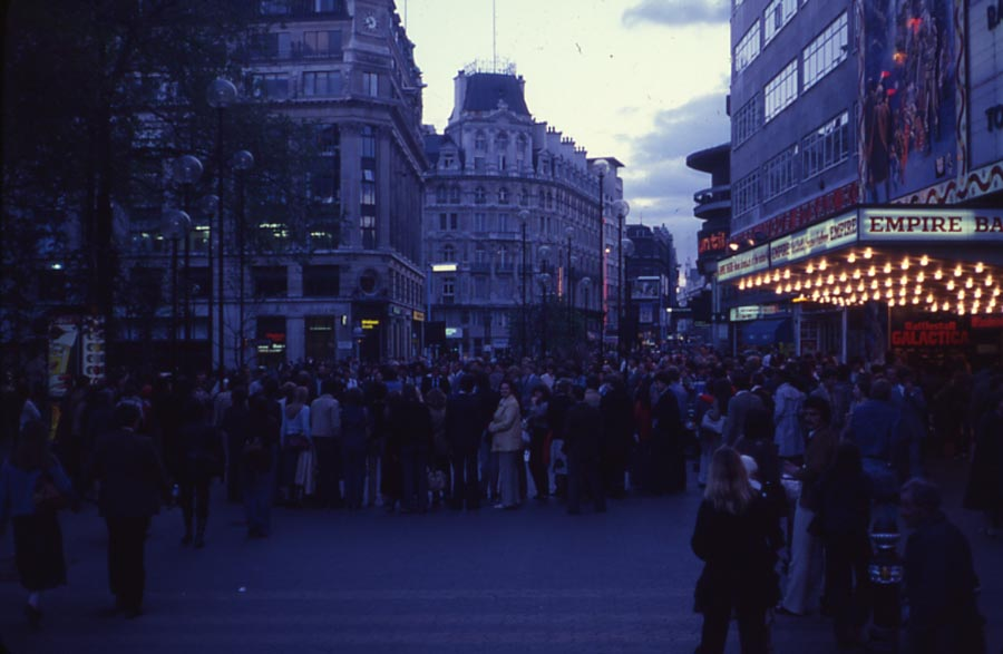 a dark and gloomy photo of crowds outside a cinema in a square
