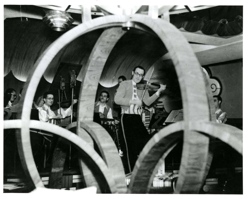 a photo of an orchestra palying an on bandstand seen through a curved wooden ornament