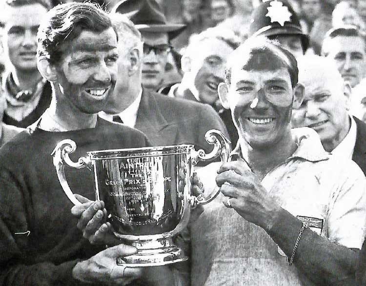 a photo of two smiling and poil covered men holding a trophy