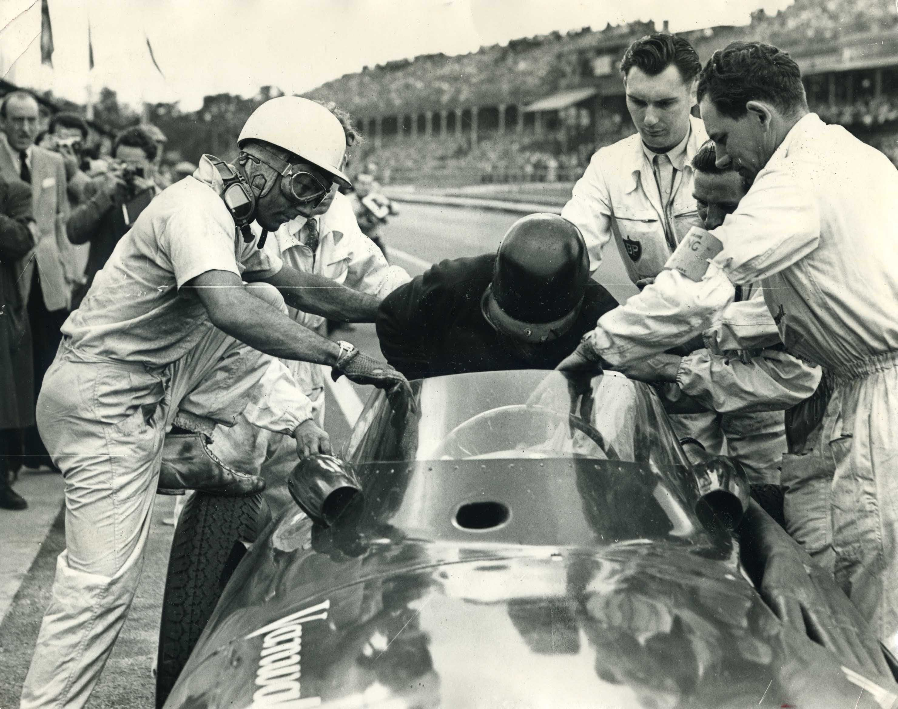 a black and white photo of two men exchanging an old formula one car