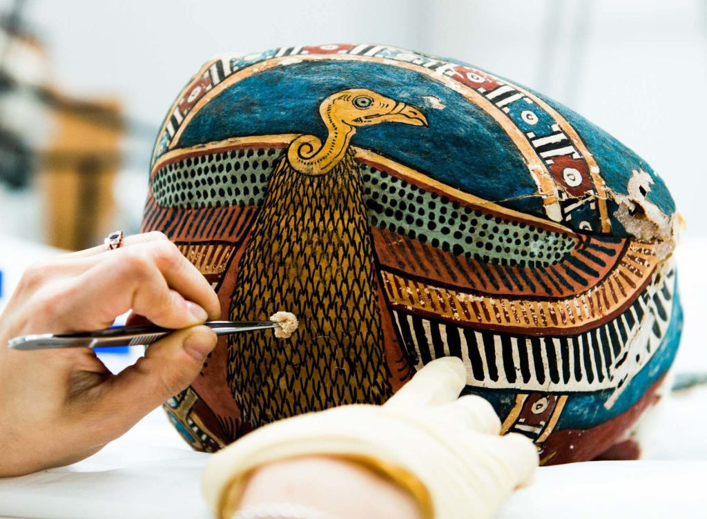 a photo of an Egyptian mask being renovated