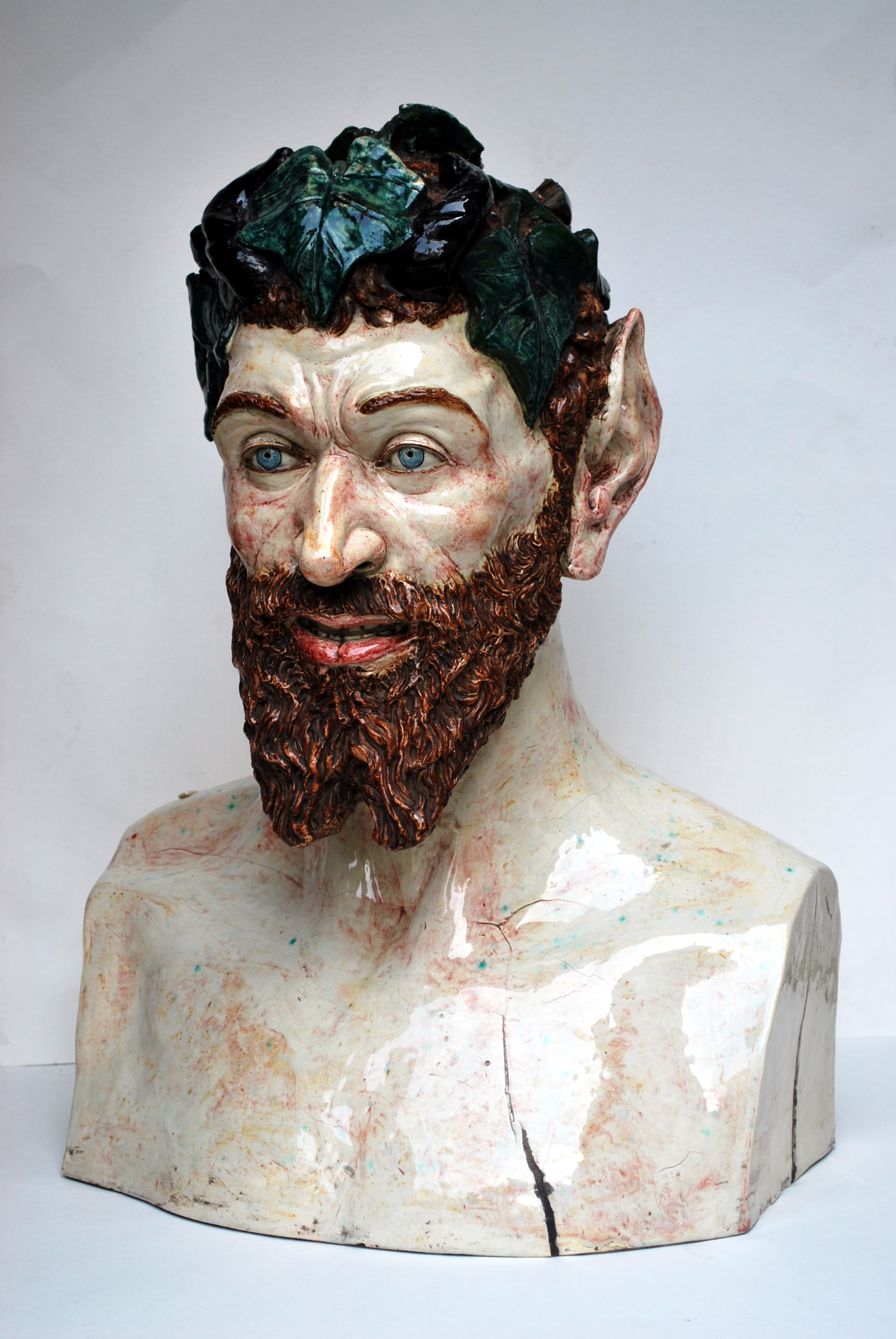 a ceramic bust of pan with pointy ears and beard