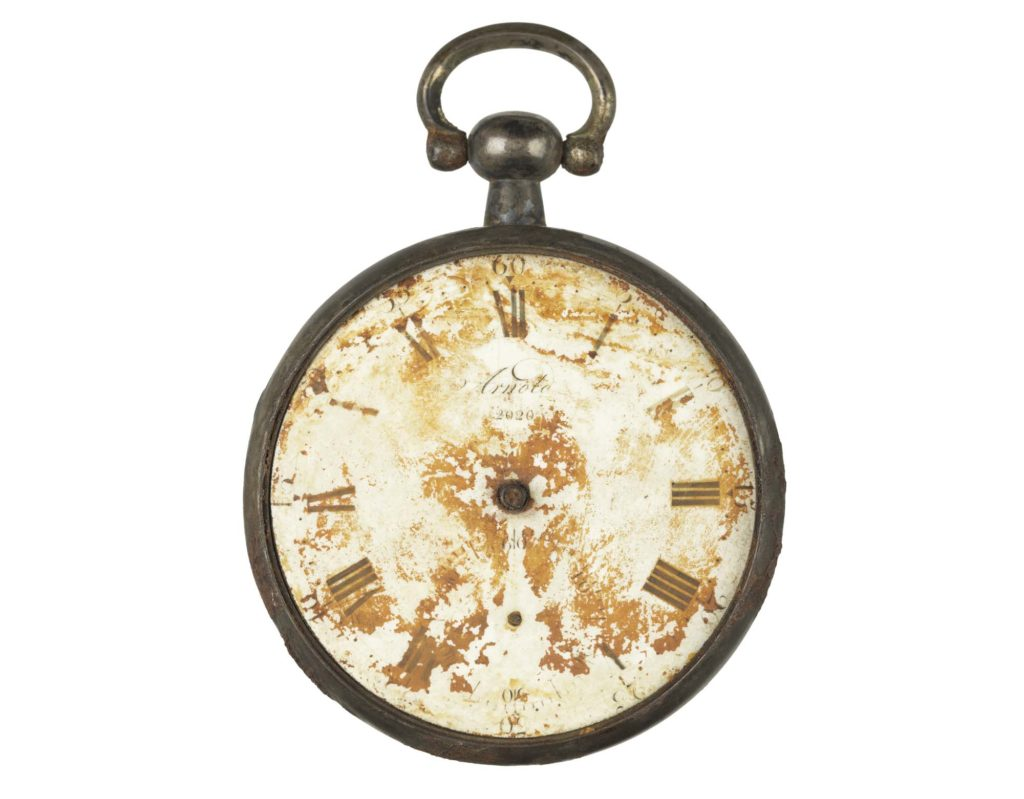a photo of an old fob watch with no glass or hands