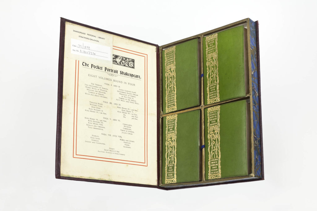 a small box containing four small miniature green bound books
