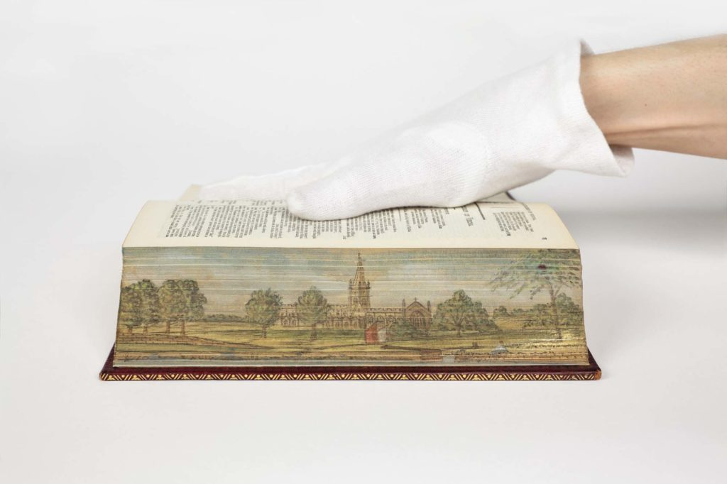 a photo of a book with a painting of a country scen with church on its fore edge