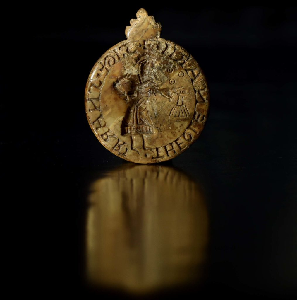 a photo of a rounbd seal with Viking Nordic script on it