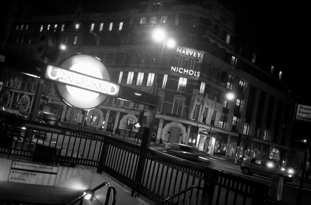 a black and white photo of a London underground entrance with cars travelling past