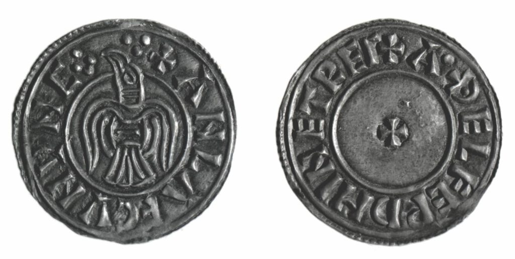 a photoof either sides of a silver coin with Viking numerals on it