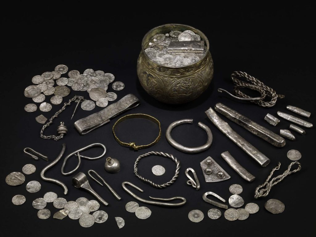 a photo of a hoard of silver jewellery next to a bowl