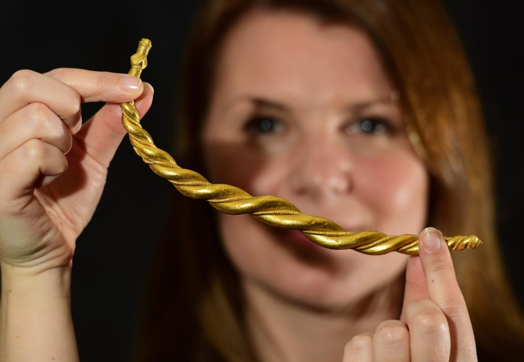 a photpo of a woman holding a twisted gold torc