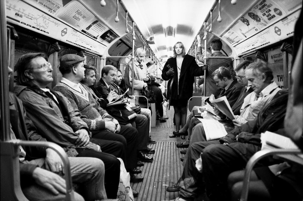 a photograph of a crowded underground carriage with a woman standing at the doorway staring down the carriage