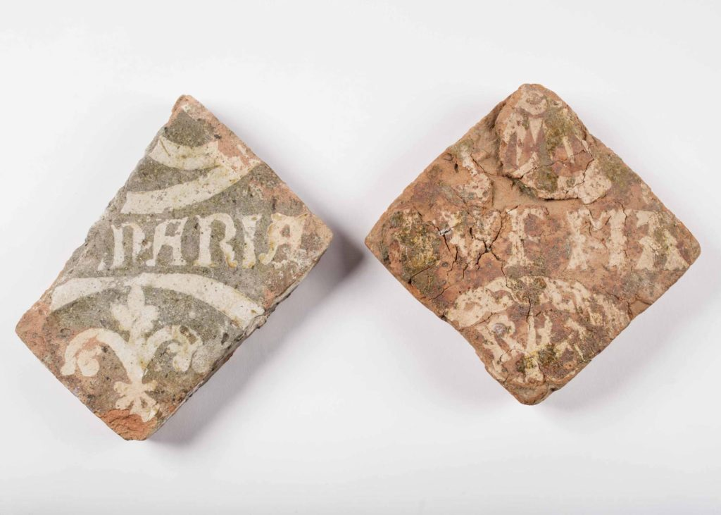 a photo of two medieval tile fragments