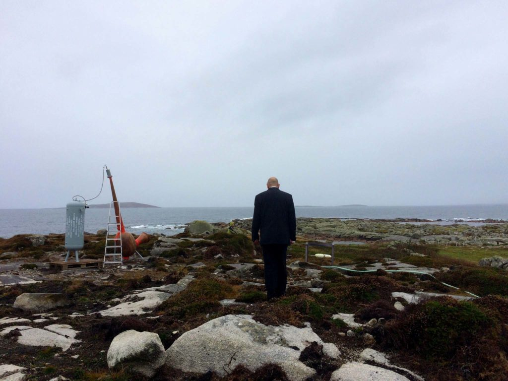 a photo of a man on a headland looking out to sea