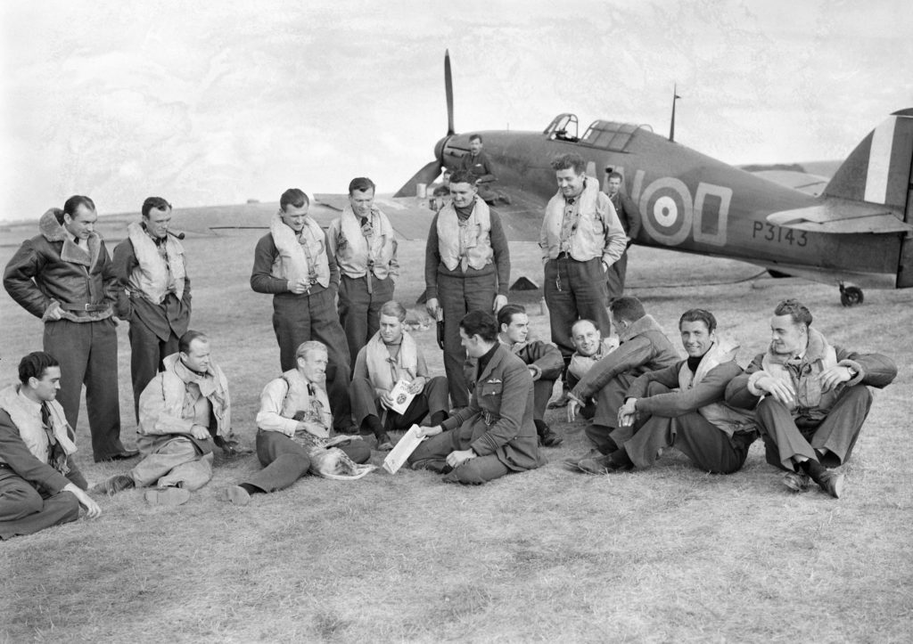 a photo of a group of RAF pilots standing and seated relaxed with a Hurricane fighter in the background