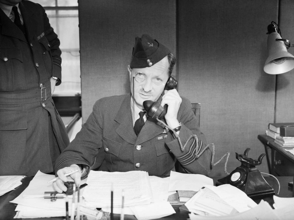 a photo of a man in an RAF uniform and monocle on the phone