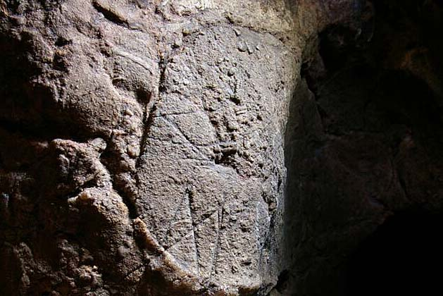 a photo of a rck with a 'w' scratched into its surface