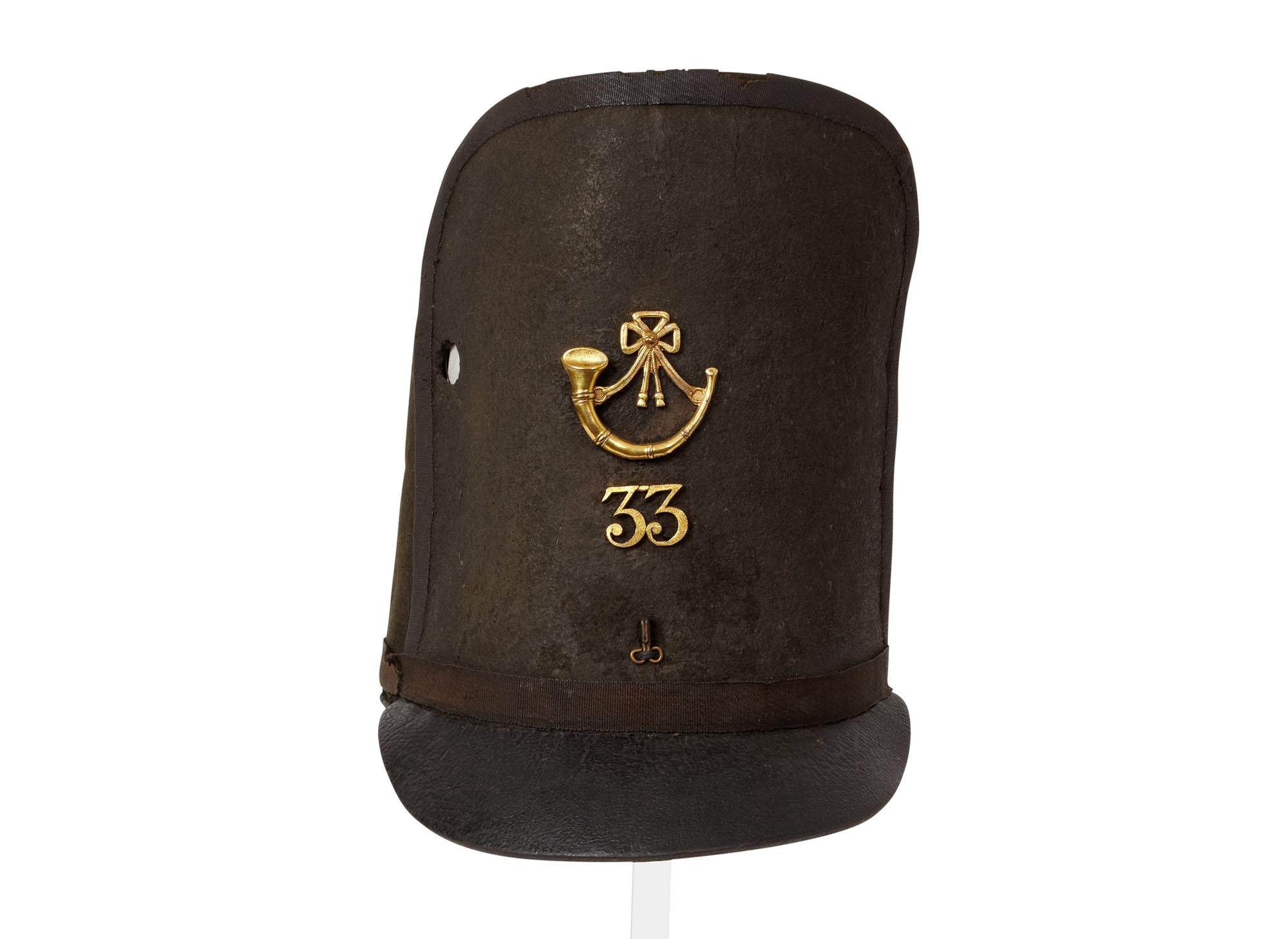 a photo of a tall felt cap with a bullet hole in the side