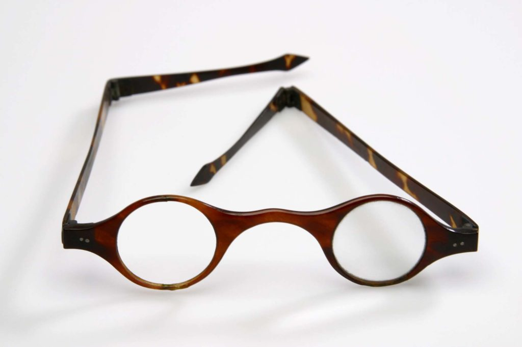 Pair of tortoiseshell-framed spectacles that belonged to John Dalton photographed on a white background.