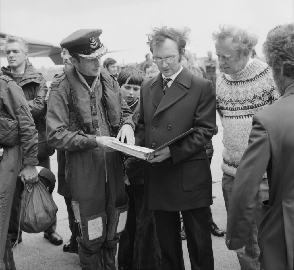 a black and white photo of a man in coat stading next to an RAF pilot offcier in flight suit and cap as onlookers crowd round