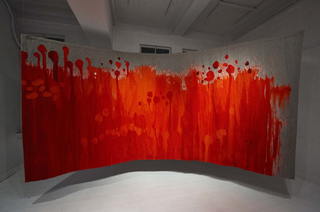 a photo of a tapestry by Misao Wtanabe in oranges and reds