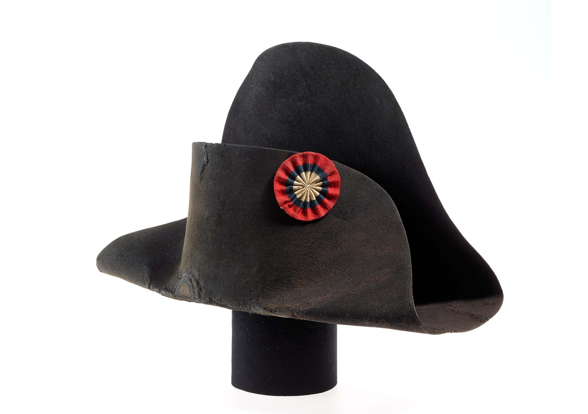 a photo of a bicorn hat with small rosette on it