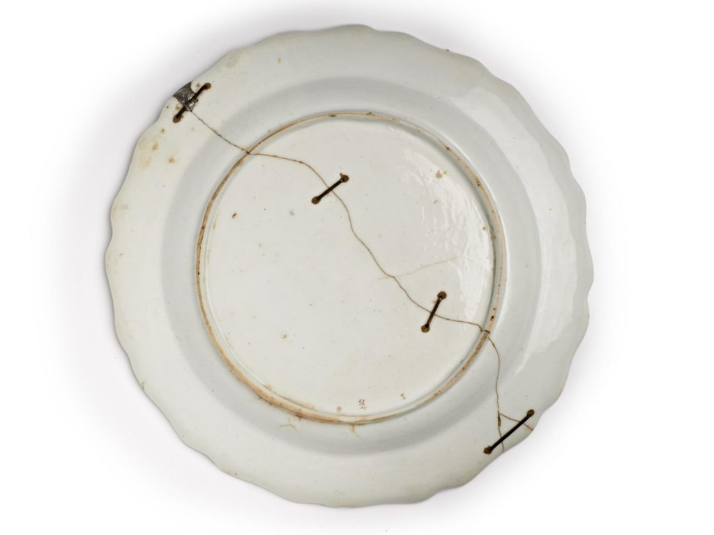 a photo of the underside of plate with staples in it repair a major crack running across its centre