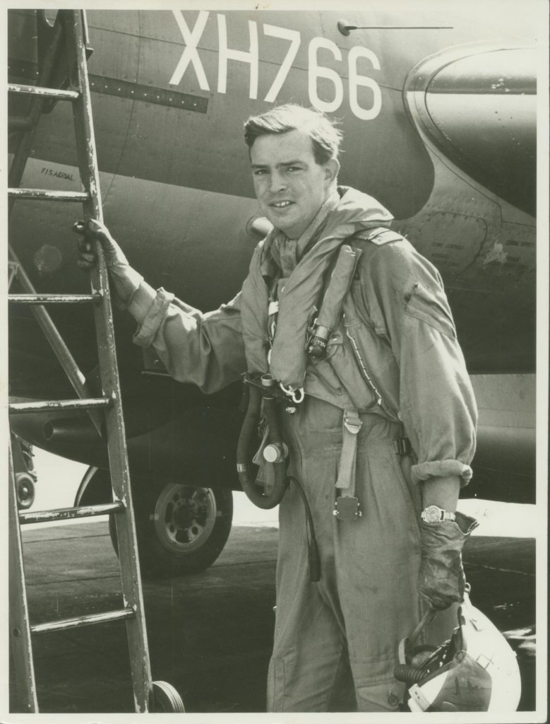 a photo of a pilot with flight suit and helemt in had leaning against the ladder of a jet plane