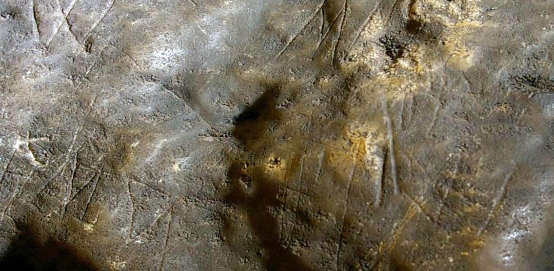 a close up photoof rocks with markings scraped into it