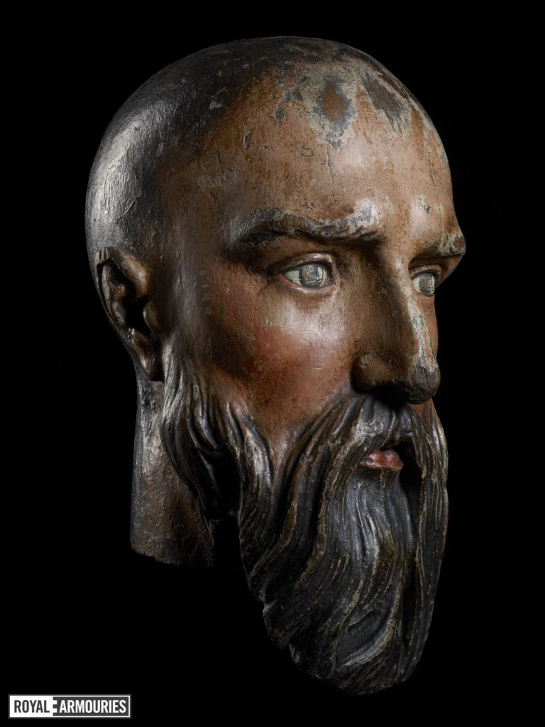 a carved ad painted wooden head of a man with a beard
