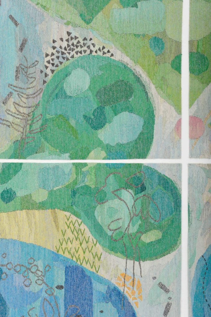 a detail of a tapestry with abstract green shapes and flowers