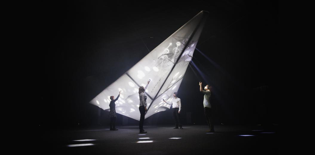 a photo of people shining torches at an illuminated palne shaped structure in a darkened room
