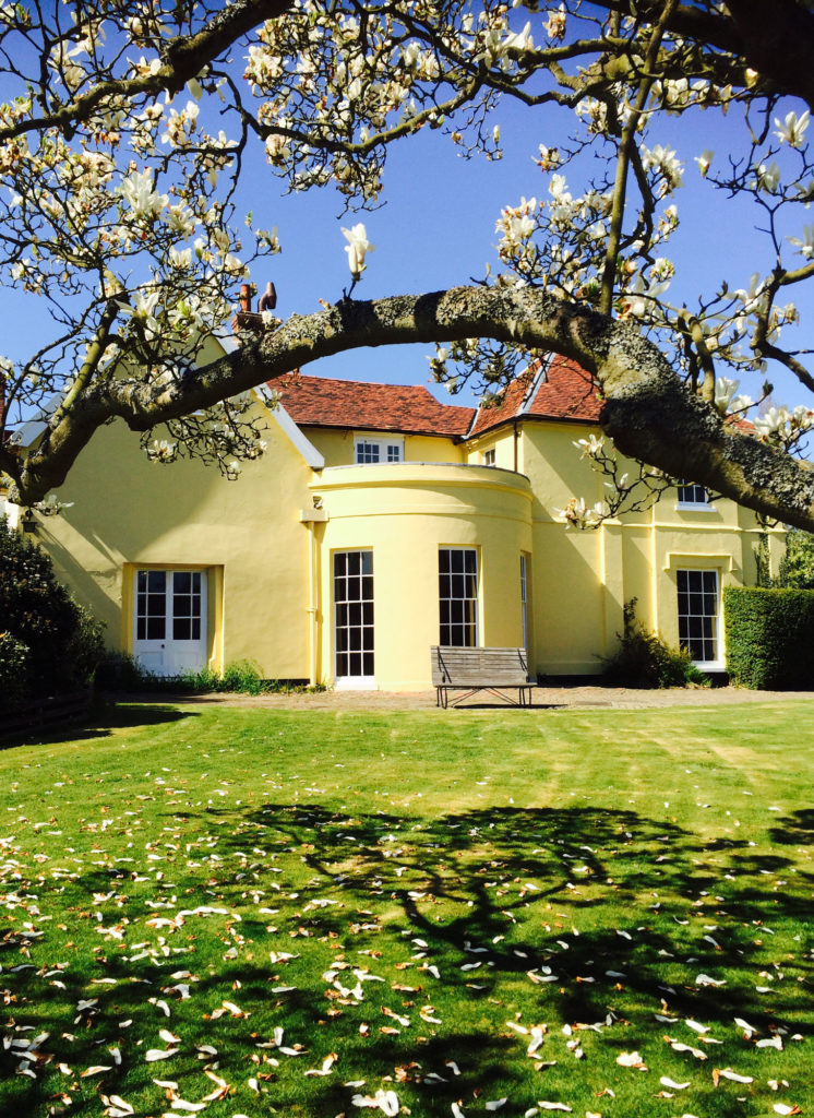 photograph of exterior of yellow house in a sunny garden, with magnolia tree in foreground
