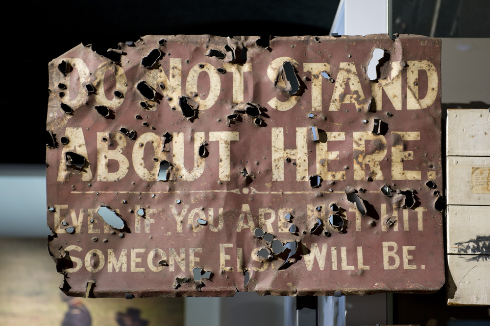 A sign from the battlefield, littered with bullet holes, it reads 'Do not stand about here, Even if you are not hit someone else will be'