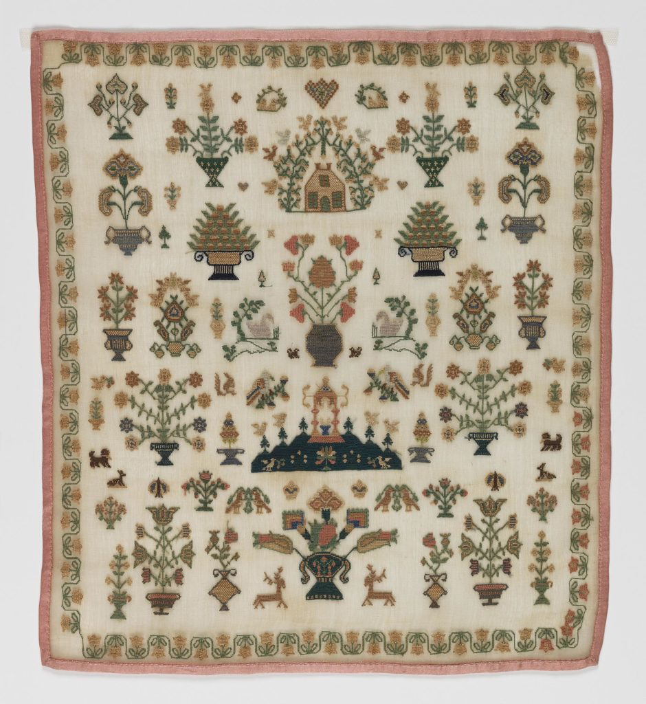 a sampler featuring embroidered trees and other motifs