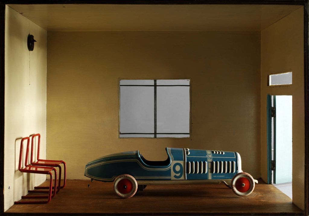 a photo of a model car in a garage of dolls house