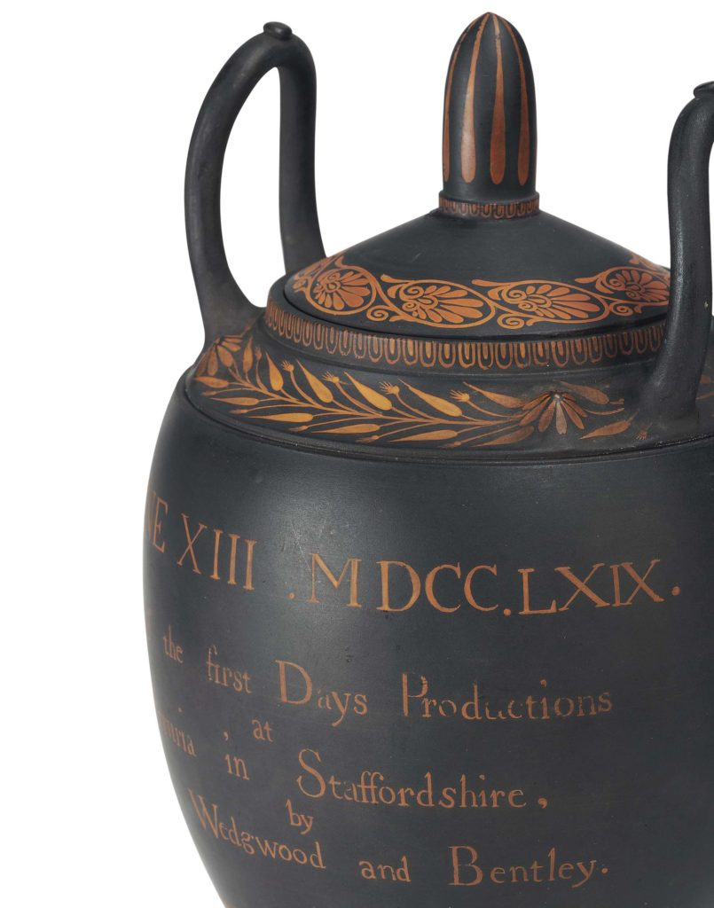 a close up of a Greek styled urn with some writing on it
