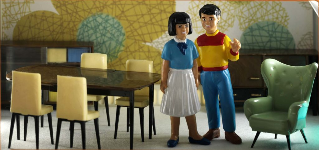 a photo of two small dolls stadning in a 1960s-styled dining room
