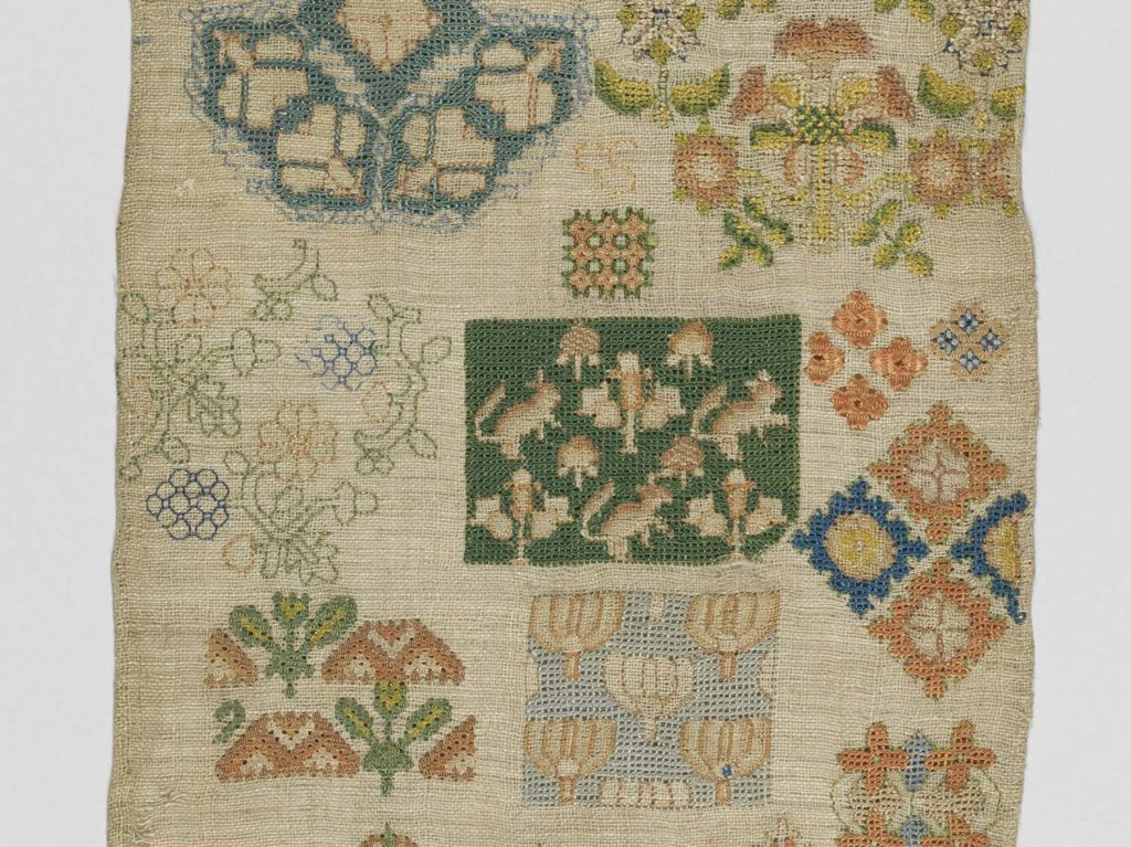 a detail of sampler showing panels of embroidered detail