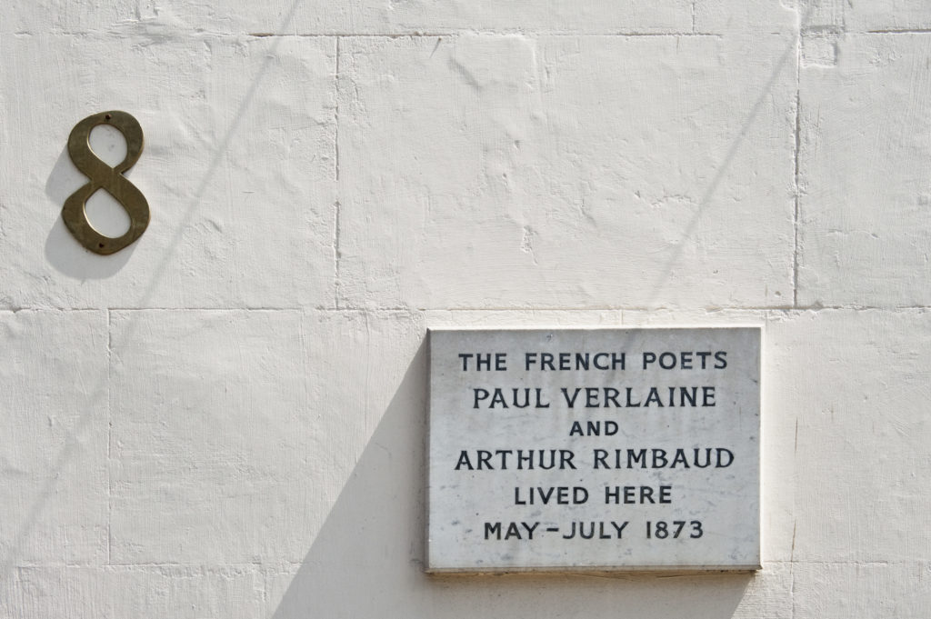 photograph of exterior of white-house with brass number '8'. A plaque on the wall reads 'th rench poets Paul Verlaine and Arthum Rimbaud lived here'