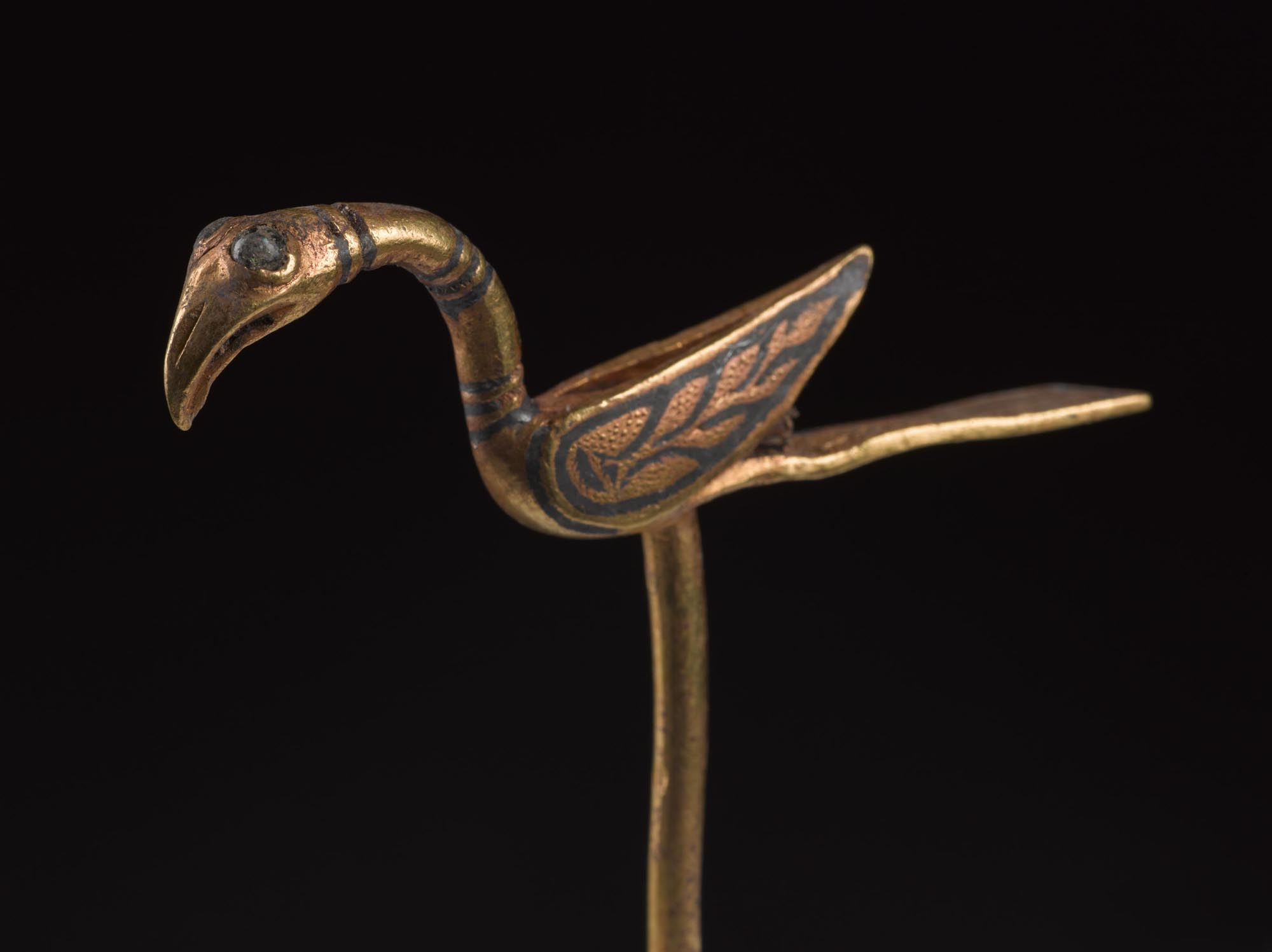 a photo of a bird brooch in gold