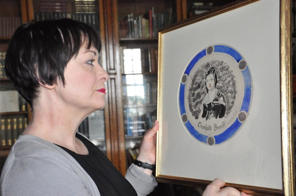 a photo of a woman staring at a round portrait of Charlotte Bronte