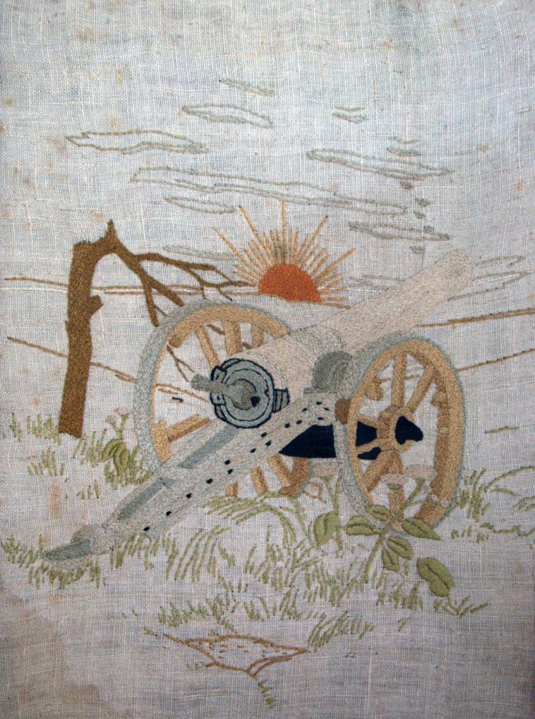 an embroidery of a shattered artillery piece with a broken tree and a sun rising in the distance